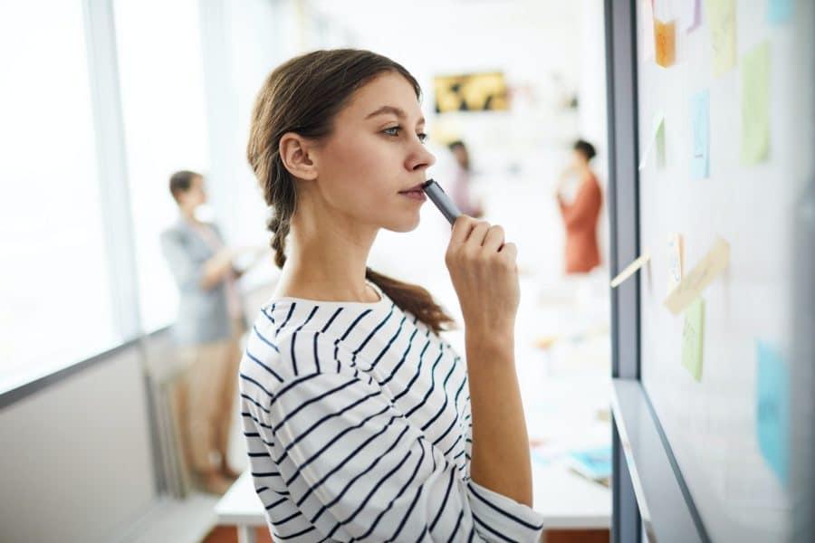 Woman visualizing digital marketing strategy on whiteboard