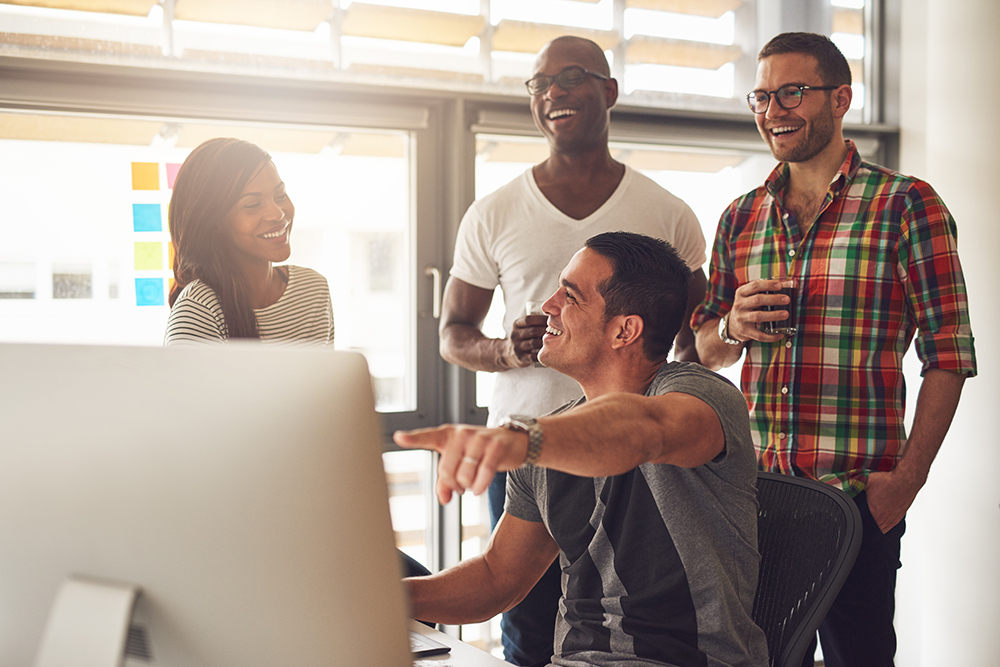 Man showing something on computer to happy friends fnwyum2