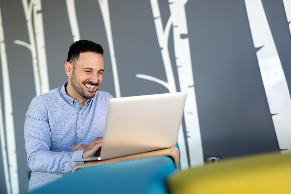 Smiling male blogger keyboarding article in electr fj3ah8p