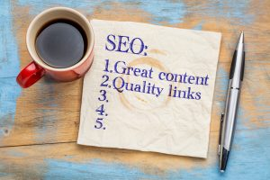 SEO Tools (search engine optimization) tips (great content and quality links) on napkin with a cup of coffee